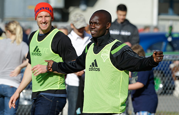 Seattle Sounders' Micheal Azira, right, of Uganda, stands with Sounders' Kenny Cooper, left, during a pickup soccer match, Monday, March 31, 2014, at a community gathering in Darrington, Wash. Players from the MLS soccer Seattle Sounders and the NFL football Seattle Seahawks visited Darrington to lend support to the town, which is located near the site of the deadly mudslide that hit the community of Oso,Wash. on March 22, 2014.