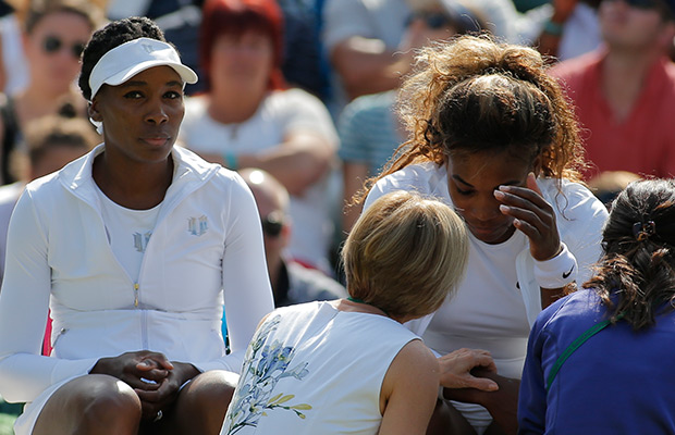 Court officials talk to Serena Williams and Venus Williams, left, of the U.S as they retire after 3 games from their women's doubles match against Kristina Barrois of Germany and Stefanie Voegele of Switzerland at the All England Lawn Tennis Championships in Wimbledon, London, Tuesday July 1, 2014.