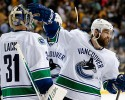 Vancouver Canucks left wing Chris Higgins, right, congratulates goalie Eddie Lack (31), of Sweden, after beating the Nashville Predators 5-4 in a shootout at an NHL hockey game Tuesday, March 31, 2015, in Nashville, Tenn.