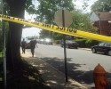 """A Baltimore Police officer follows a man, who screamed """"Let me in! I'm going in!"""" before crossing the yellow tape and walking into the crime scene on the 100 block of Upmanor Road, in Baltimore, where a young boy and a 31-year-old woman were shot and killed, Thursday, May 28, 2015. In the month since Freddie Gray died and the city erupted in civil unrest, Baltimore has seen its murder rate skyrocket. There have been 36 murders in May alone."""
